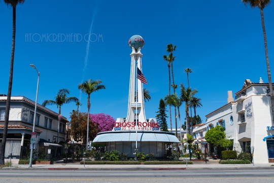"A rounded front building faces the street, atop it a tall spire stretches toward a bright blue sky. Near the bottom red letters spell out ""Crossroads of the World."" Atop the spire a globe."