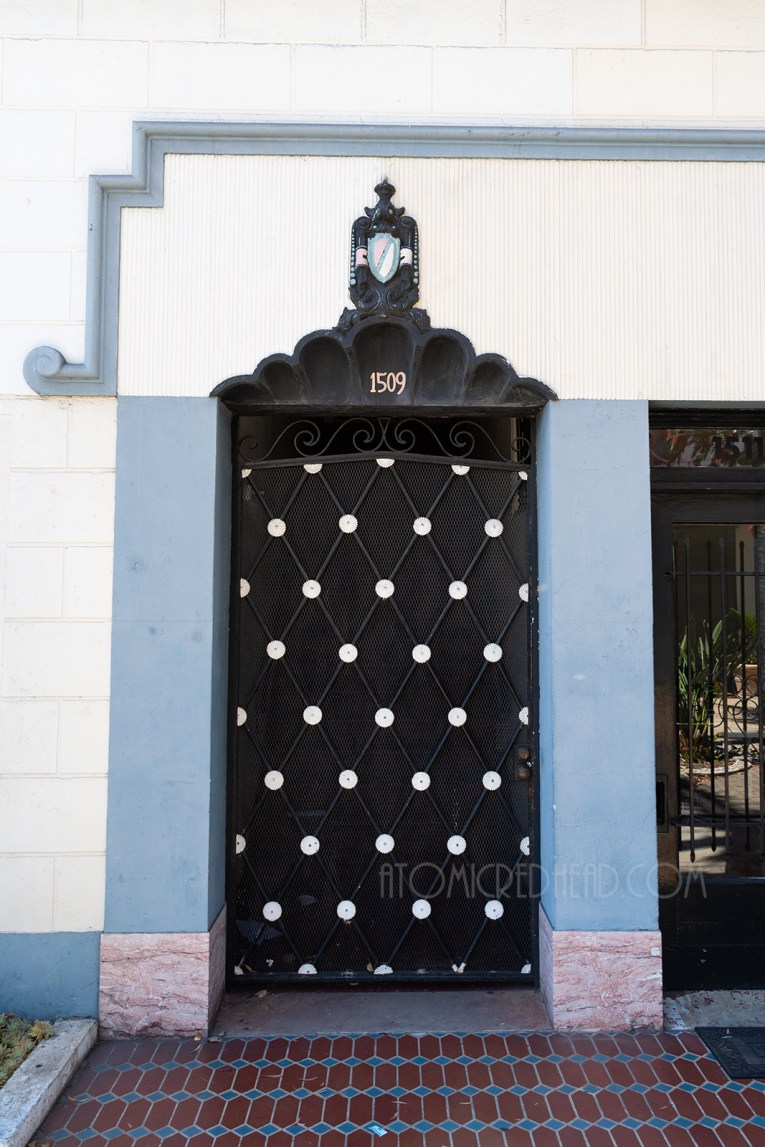A tall black gate with a diamond pattern. Above, a shell like alcove with a shield above it.