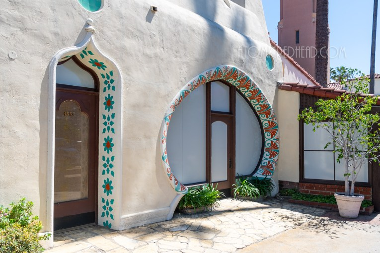 The Middle Eastern facade, which features a large rounded window with door in the middle. Along the edge of the window are swooping decorative designs painted in teal and orange.