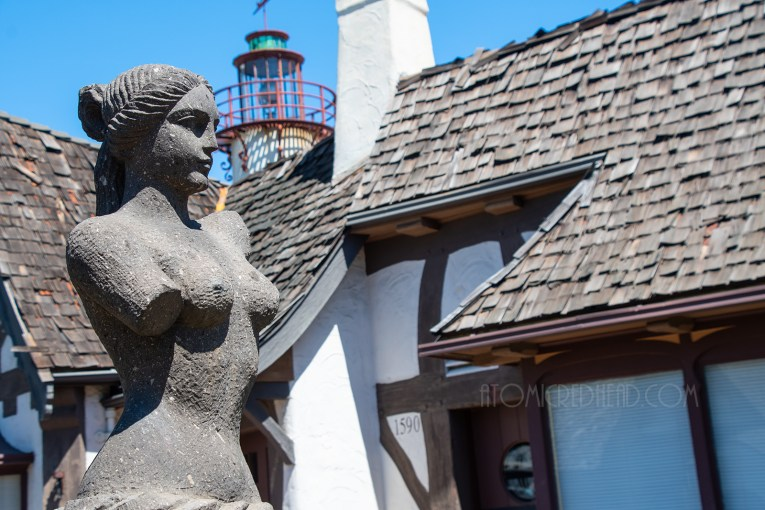 Close-up of a statue of nude woman, the Cape Code facades in the background, and in the slight distance a towering lighthouse.