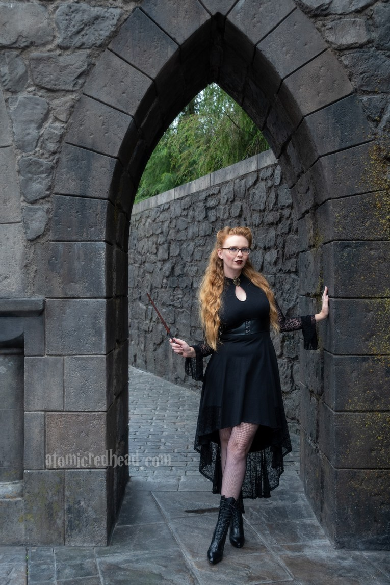 Myself standing in an archway of dark stone, wearing a black high-low dress with lace sleeves, and a key hole cut out at the neck, that features a gold brooch with a purple stone, fishnets, and a mid-calf hight Victorian style lace up boots.