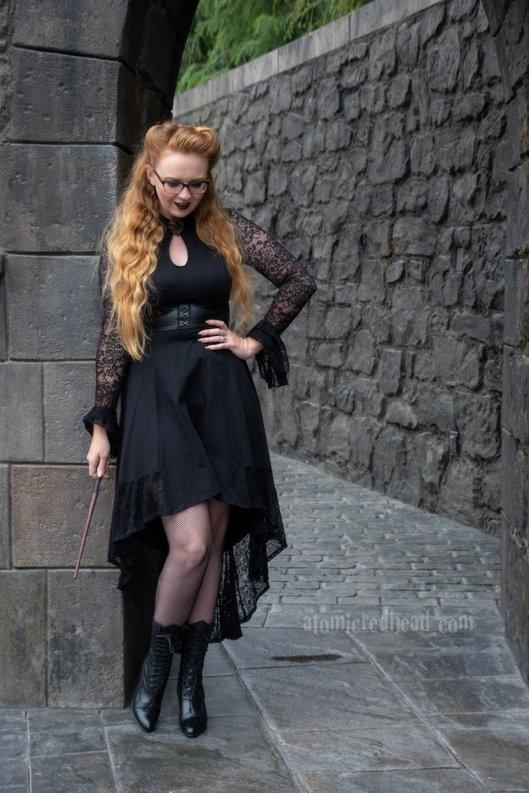 Myself standing against a dark stone building, wearing a black high-low dress with lace sleeves, and a key hole cut out at the neck, that features a gold brooch with a purple stone, fishnets, and a mid-calf hight Victorian style lace up boots.
