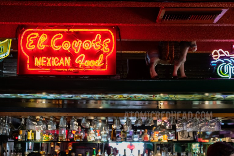 """A red neon reading """"El Coyote Mexican Food"""" glows above a bar."""