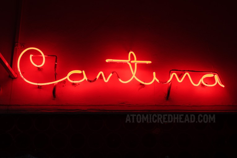 "Glowing red neon reads ""Cantina"""