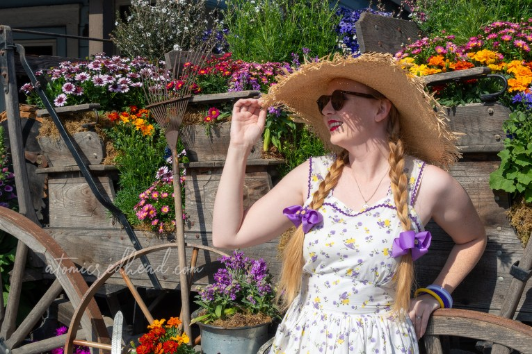 Myself, standing next to a floral arrangement in Ghost Town, wearing a large straw hat and white dress with a yellow and purple floral and straw hat print.