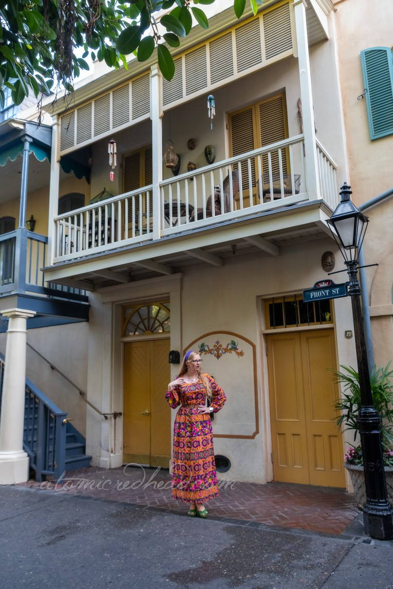 Myself, wearing a purple, yellow, pink, and green psychedelic printed maxi dress with a purple scarf in my hair, standing under a balcony in New Orleans Square.