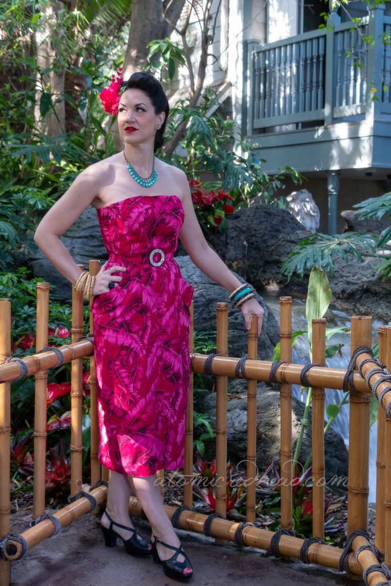 Nikki, a tall raven haired beauty, stands in the jungle of Adventureland wearing a strapless dress made of pink palm print fabric. A bright pink flower in her hair.