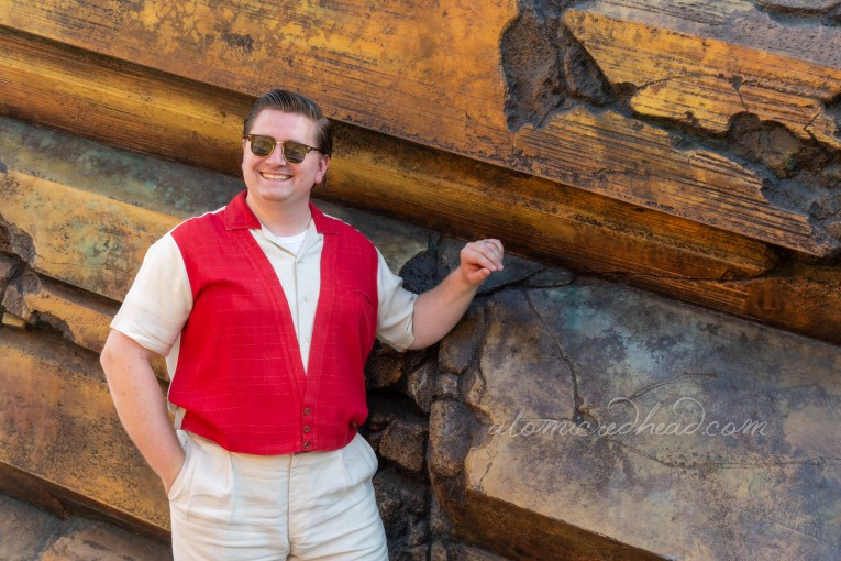 Patrick, wearing a red and white shirt and white pants leans against the golden rocks that flank the entrance to Tomorrowland.