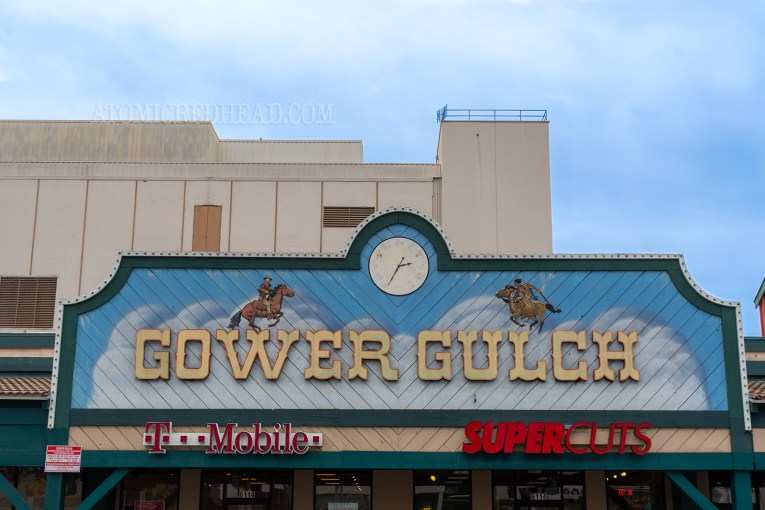 "A large sign above the stores reads ""Gower Gulch"" in yellow western style letters. Above the letters are painted images of cowboys on horseback. A white clock face with various icons of the west serve as the numbers."