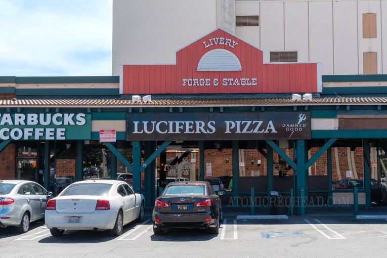 "Above Lucifer's Pizza, one of the real establishments, sits a sign reading ""Livery Forge & Stable"""