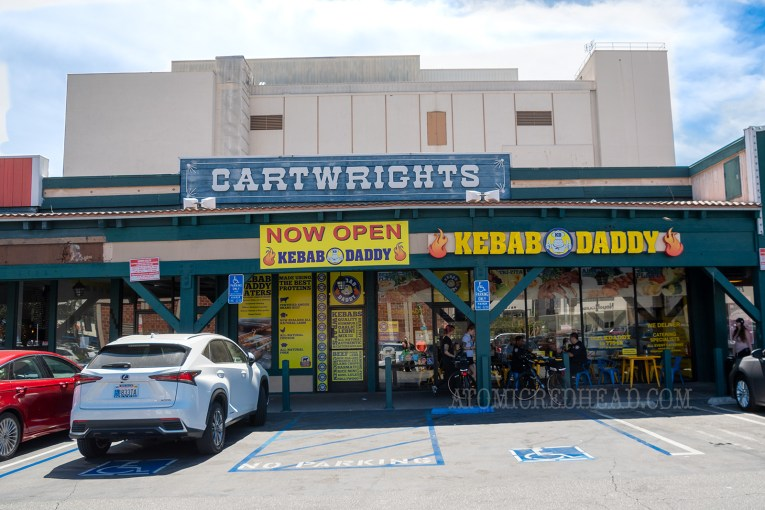 "Above a sea food restaurant is a blue and white sign reading ""Cartwrights"""