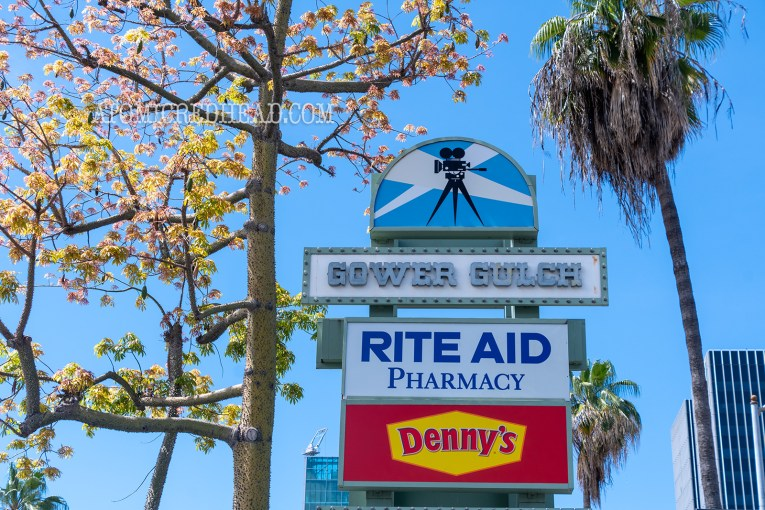 """A tall sign features an image of a movie camera, and below it reads """"Gower Gulch"""" and smaller signs for """"RIte Aid"""" and """"Denny's"""" below."""