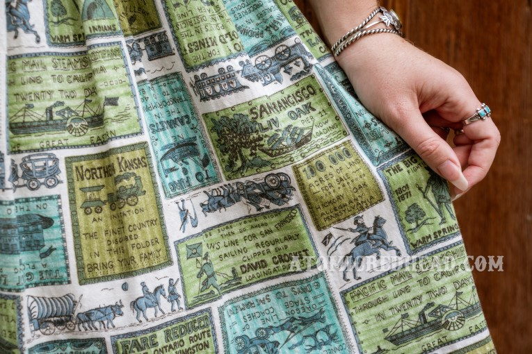 Close-up of my dress, which features blue and green boxes, that have western themed images and text in them, some of which are faux adverts.