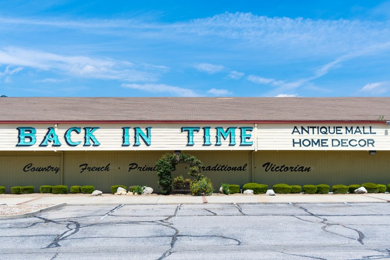 "A large tan building has large blue letters painted across it reading ""Back in Time antiques home decor."" Below in black script reads ""Country French Traditional Provincial Victorian"""