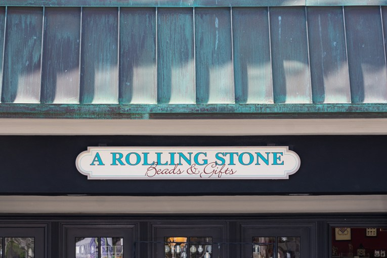 "A copper roof that has turned green sits atop a white sign reading ""A Rolling Stone Beads & Gifts"""