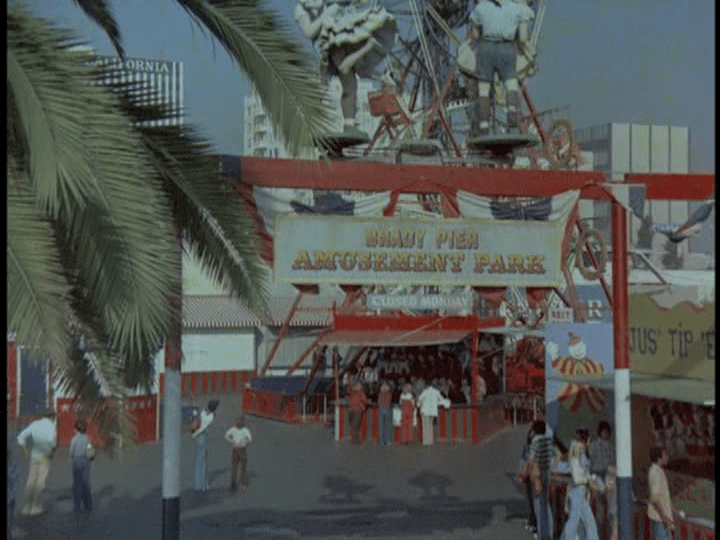 "Screencap: Carnival rides scattered in the background, a banner reads ""Brady Pier Amusement Park"""