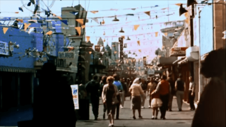 Screencap: The midway of The Pike, with flags stretched across the thoroughfare.