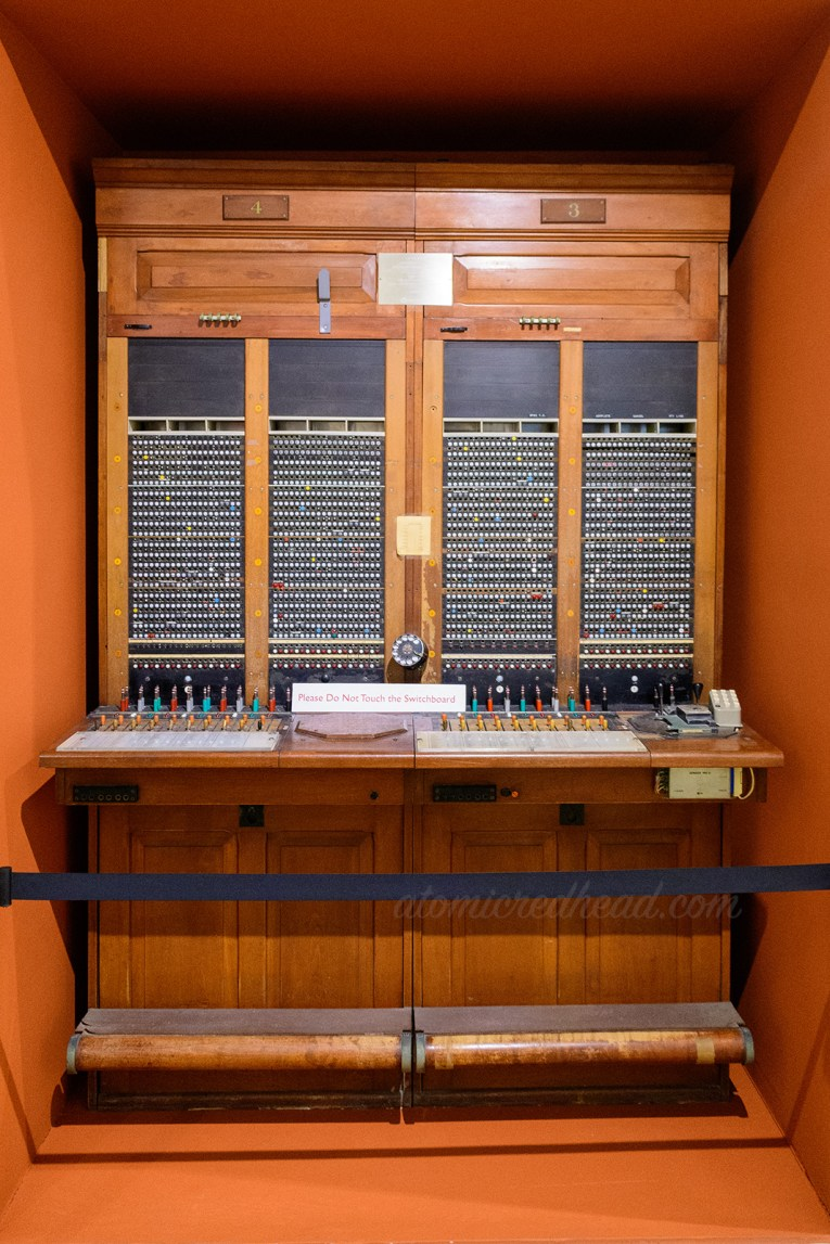 The switchboard, made of wood, and full of various lights and plugs.