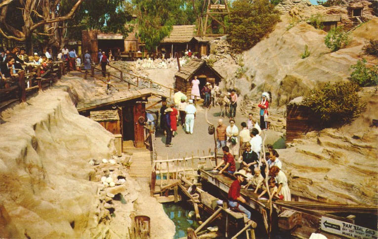 Man made rock formations surround a sluice box where men in wester attire help guests pan for gold.
