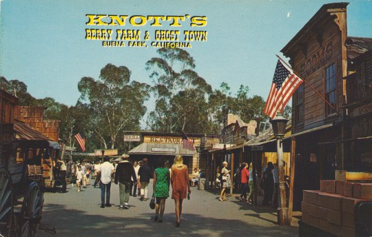 "Guests walk down an old western street. Yellow text reads ""Knott's Berry Farm & Ghost Town Buena Park, California"""