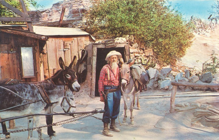 An old miner with a grey beard stands with a pair of donkeys in front of a mine entrance.