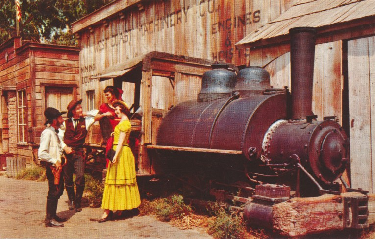 Two cowboys talk to two well dressed ladies near an old borax train.