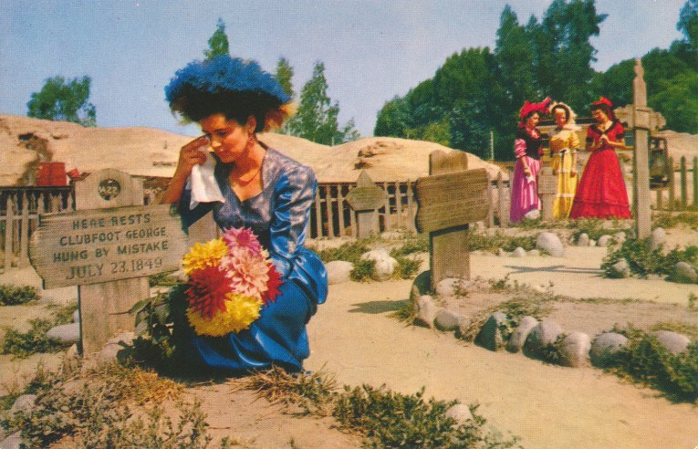 Women in old western attire weep at the graves of Boot Hill.
