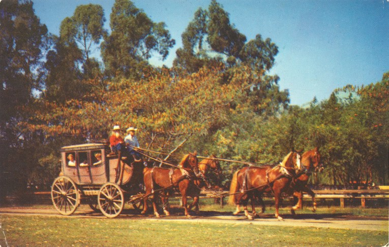 A stagecoach pulled by four brown horses.