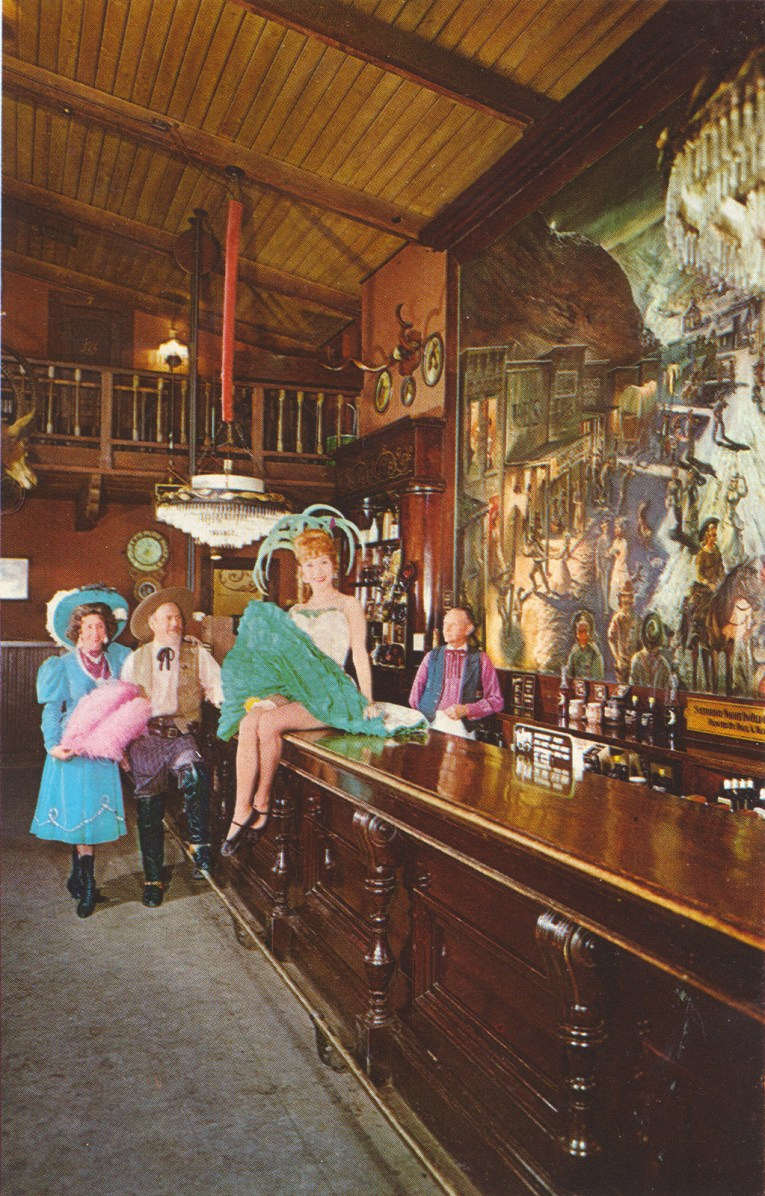 Inside the Calico Saloon, can-can girls sit on the bar.
