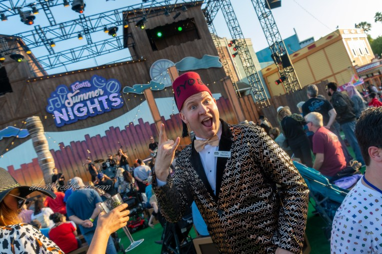 The head of the party planning committee, Duncan Disorderly, wearing a red fez, and gold and black tuxedo jacket, dances to the live music.