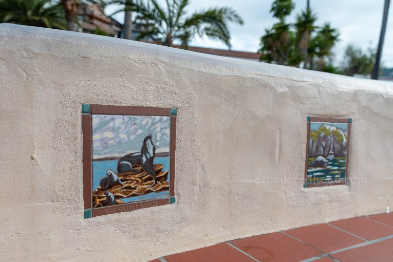 Colorful tiles featuring images of sea lions are set into an adobe walled bench.