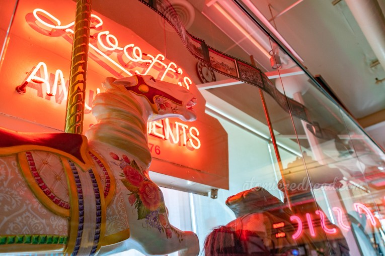 "A carousel horse stands in front of a vintage neon sign reading ""Looff's Amusements"""
