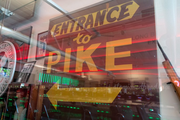 "Vintage maroon sign reading ""Entrance to Pike"" in yellow letters."