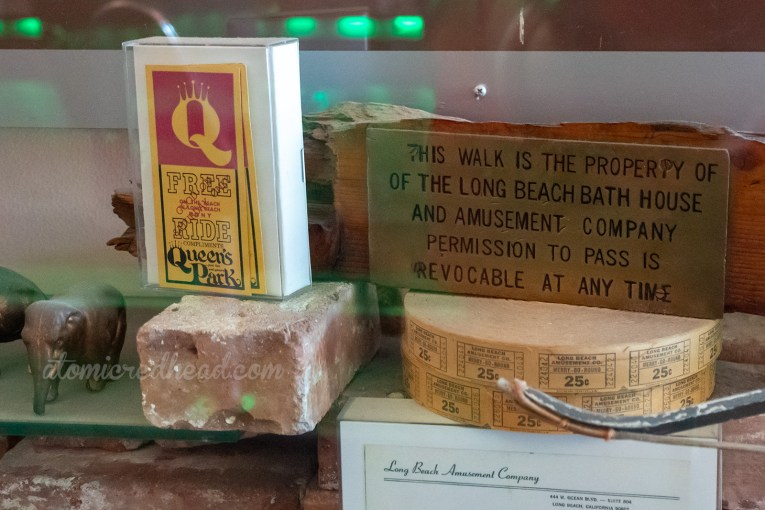 "A vintage ticket from The Pike , a piece of wood with a brass plaque mounted on it reading ""This walk is property of the Long Beach Bath House and Amusement Company Permission to pass is revokable at any time"" and a roll of merry-go round tickets."