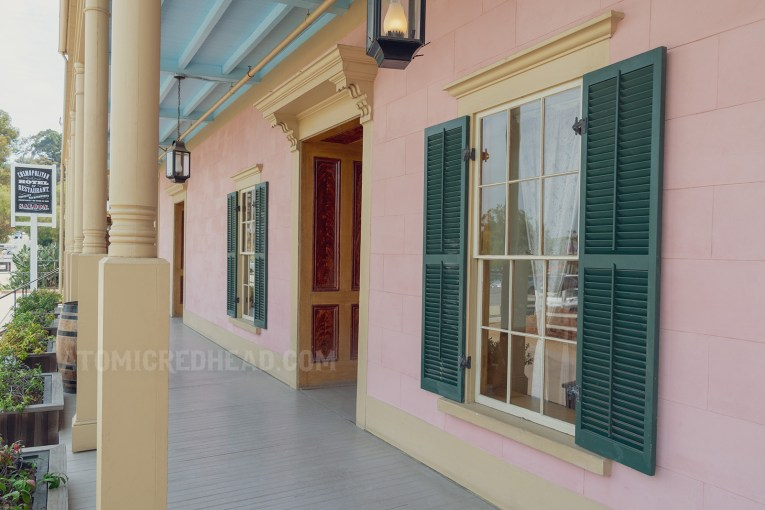 Exterior promenade, pink walls, green shutters, and pale yellow trim around the doors and windows.