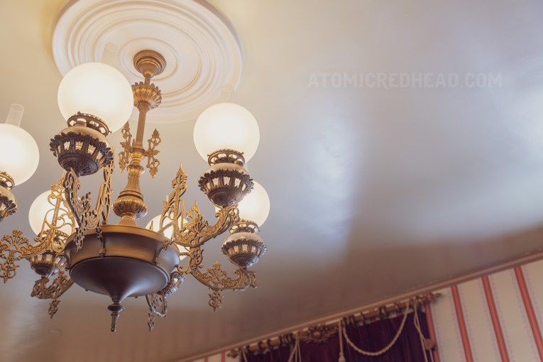 Close up of the brass and glass chandelier, scroll works details the brass which large white globe like shades sit upon.