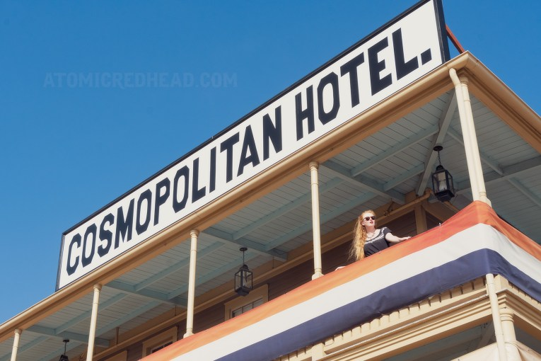 "Myself standing on the outer balcony of the hotel, wearing a black dress with silver trim. A massive white sign reads ""Cosmopolitan Hotel"" in black letters."