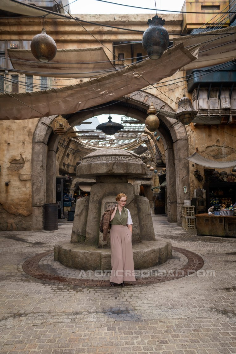 Myself standing in the marketplace of Batuu, wearing a dark brown motorcycle jacket, a green and white blouse, and tan wide leg slacks. Swaths of fabric and nets hang between the stonework stalls on either side, giving an almost Middle Eastern marketplace vibe