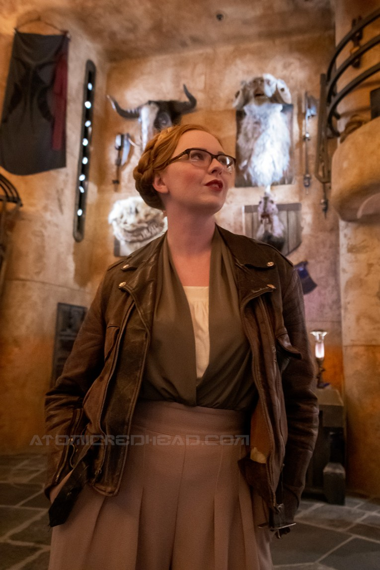 Myself standing inside Dok-Ondar's Den of Antiquities, wearing a dark brown motorcycle jacket, a green and white blouse, and tan wide leg slacks.