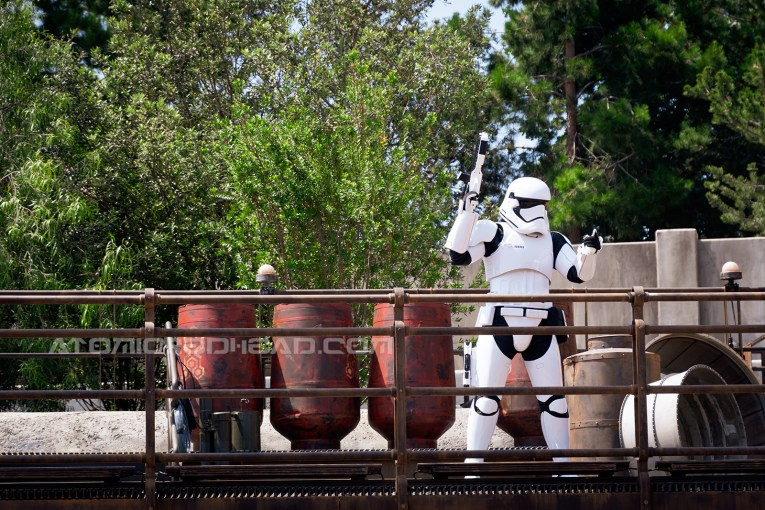 A stormtrooper talks to a visitor of Batuu from a raised platform.