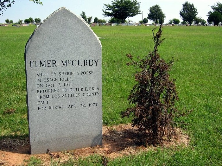 "Elmer McCurdy's grave, a grey headstone reading ""Elmer McCurdy shot by sheriff's posse in Osage Hills on Oct. 7 1911 Returned to Guthrie, Okla. from Los Angeles Calf. for burial April 22 1977"""