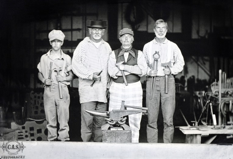 A black and white image taken by Catherine, of four men in period attire in the blacksmith shop.