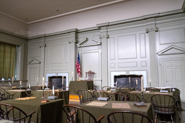 Inside the singing room, a chair and small desk sit against the back wall. The walls are painted a pale green color. In front a small collection of tables and chairs, atop each table are quills and parchment.