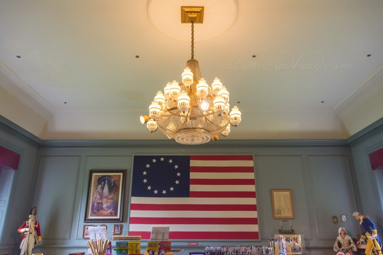 Inside the gift shop portion of Independence Hall. A massive flag, the original version, hangs on the wall. A chandelier hangs from the ceiling.