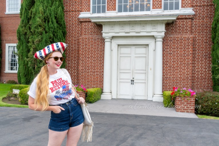 "Myself standing outside Independence Hall, a red brick building with white windows and doors, wearing a tricorn hat of red, white and blue stripes, a white t-shirt reading ""Paul Revere and the Raiders"" with the original flag jutting from the ""Raiders"" portion, and jean shorts, and platform shoes features red and white stripes and blue with white stars."