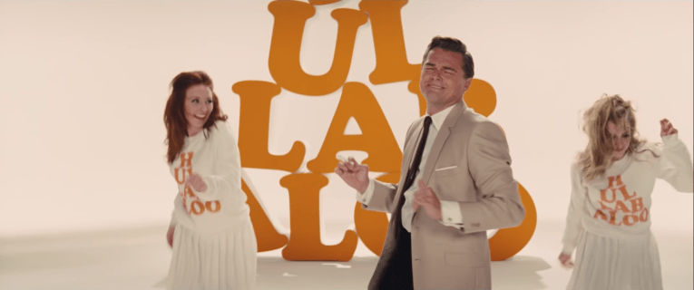 "Leonardo DiCaprio dances with two girls. DiCaprio wears an off white suit jacket, a black tie, and black pants. The girls wear oversized sweaters reading ""Hullabaloo"" in orange letters, and white skirts. The background is all white with giant orange letters spelling Hullabaloo."