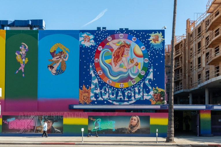 "A rainbow paint job covers the former Earl Carroll. Panels, each a different color, feature psychedelic characters, including dancers, musicians, acrobats, and jugglers. A massive painting of a nude man with long red hair pouring water from pitchers is painted on the right side, icons of astrology circle him. ""Aquarius"" is painted below him."