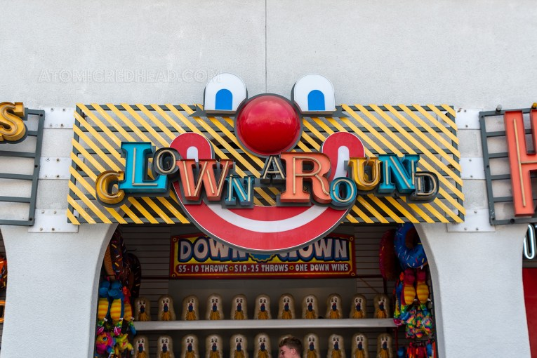 "A clown face tops the opening of a clown game titled ""Clown Around"""