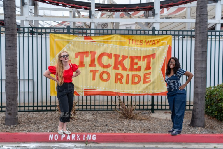 "Carla and I stand in front of a large yellow sign reading ""Ticket to Ride"""