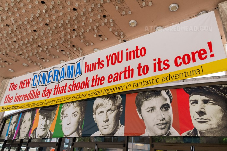 "A banner reading ""The NEW CINERAMA hurls YOU into the incredible day that shoot the earth to its core! You are there with the treasure hunters and love seekers locked together in fantastic adventure!"" and feature black and white images of the cast."